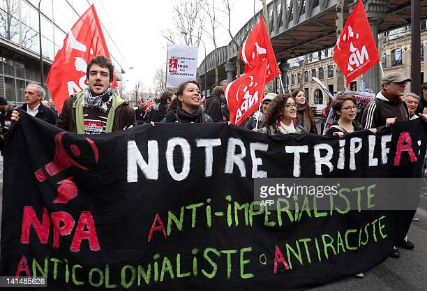 Supporters of French farleft anticapitalist NPA party hold a banner reading 'Our triple A Antiimperialist Anticolonialist Antiracist' as they take...