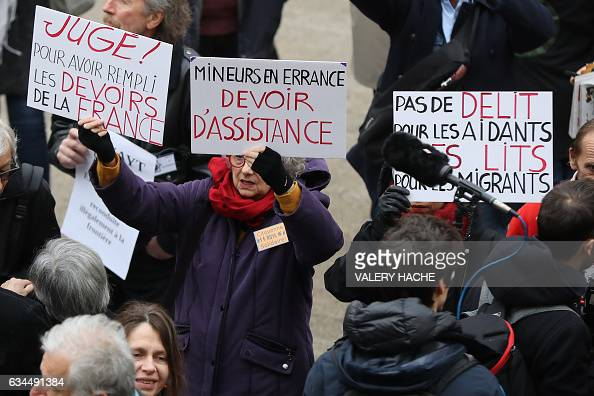 Supporters of French farmer Cedric Herrou hold signs reading 'Tried for having fulfilled the duties of France' and 'Wandering minors duty to assist'...