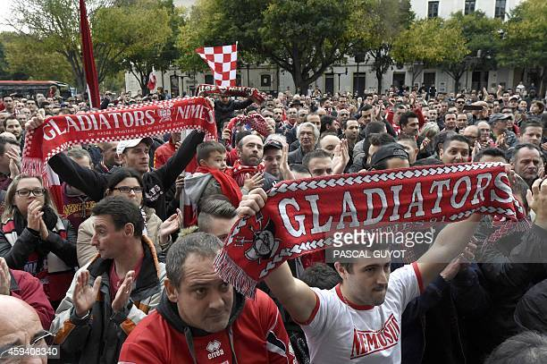 Supporters of French L2 second division football club Nimes Olympique hold scarves as they gather near the Arena of Nimes on November 22 2014 in...