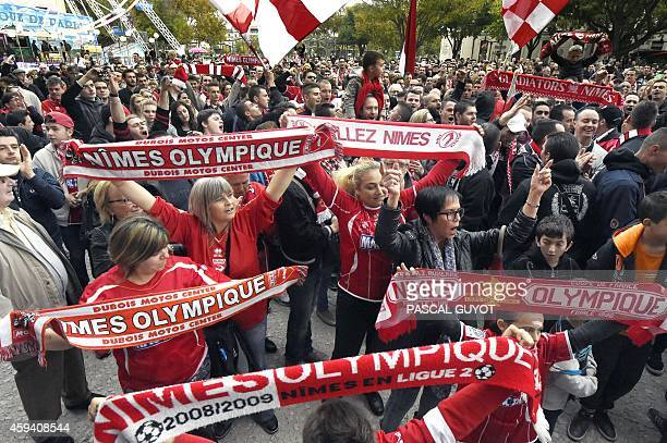 Supporters of French L2 second division football club Nimes Olympique hold the club's scarves as they gather near the Arena of Nimes on November 22...
