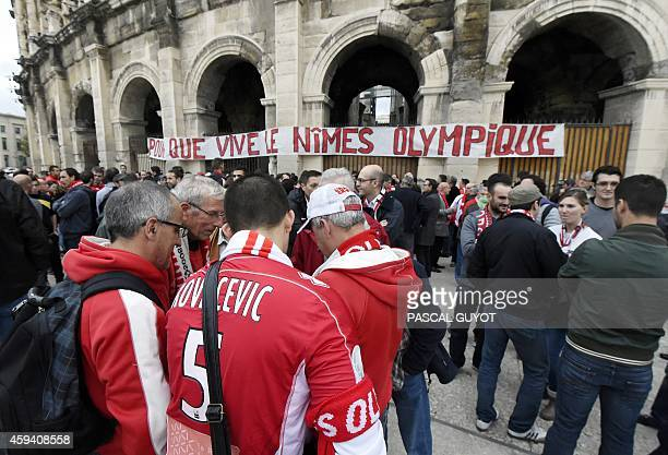 Supporters of French L2 second division football club Nimes Olympique gather near a banner hung on the Arena of Nimes reading 'So that Nimes...