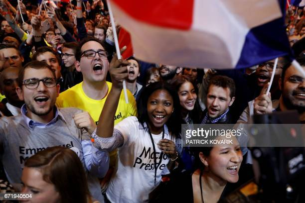 TOPSHOT Supporters of French presidential election candidate for the En Marche movement Emmanuel Macron cheer following the announcement that he was...