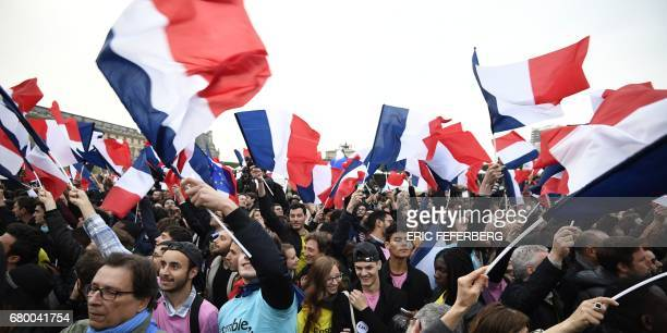 TOPSHOT Supporters of French presidential election candidate for the En Marche movement Emmanuel Macron wave French national flags as they celebrate...
