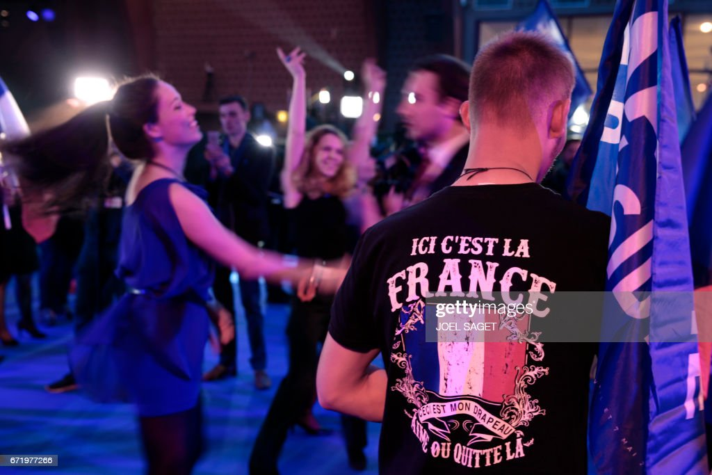 TOPSHOT - Supporters of French presidential election candidate for the far-right Front National (FN) party dance after the announcement of the first round of the Presidential election in Henin-Beaumont, on April 23, 2017. / AFP PHOTO / joel SAGET