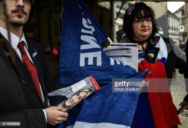 Supporters of French presidential election candidate for the farright Front National party Marine Le Pen distribute flyers on April 28 2017 in Caudry...