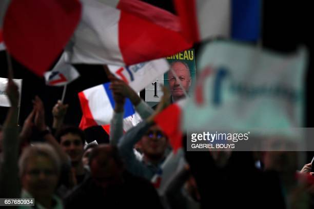 Supporters of French presidential election candidate for the Popular Republican Union party wave flags during a campaign rally on March 25 2017 in...