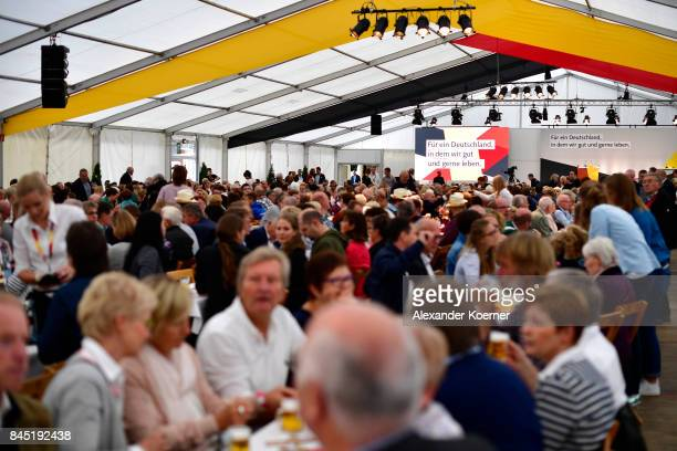 Supporters of German Chancellor and Christian Democrat Angela Merkel sit and wait prior to a speech to supporters at a fest tent during an election...