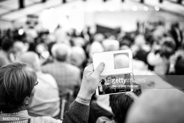 Supporters of German Chancellor and Christian Democrat Angela Merkel listen to her speech at a fest tent during an election campaign stop on...
