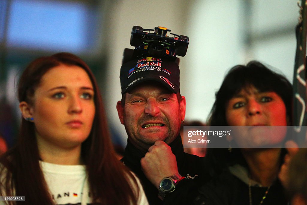 Supporters of German Formula One driver Sebastian Vettel cheer during a public viewing in Vettel's home town on November 25, 2012 in Heppenheim, Germany.