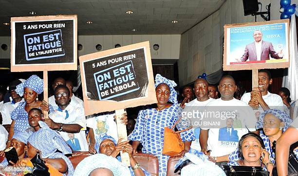 Supporters of Guinean opposition politician Sidya Toure of the Union of Republican Forces party holds up placards reading ' Five years for nothing we...