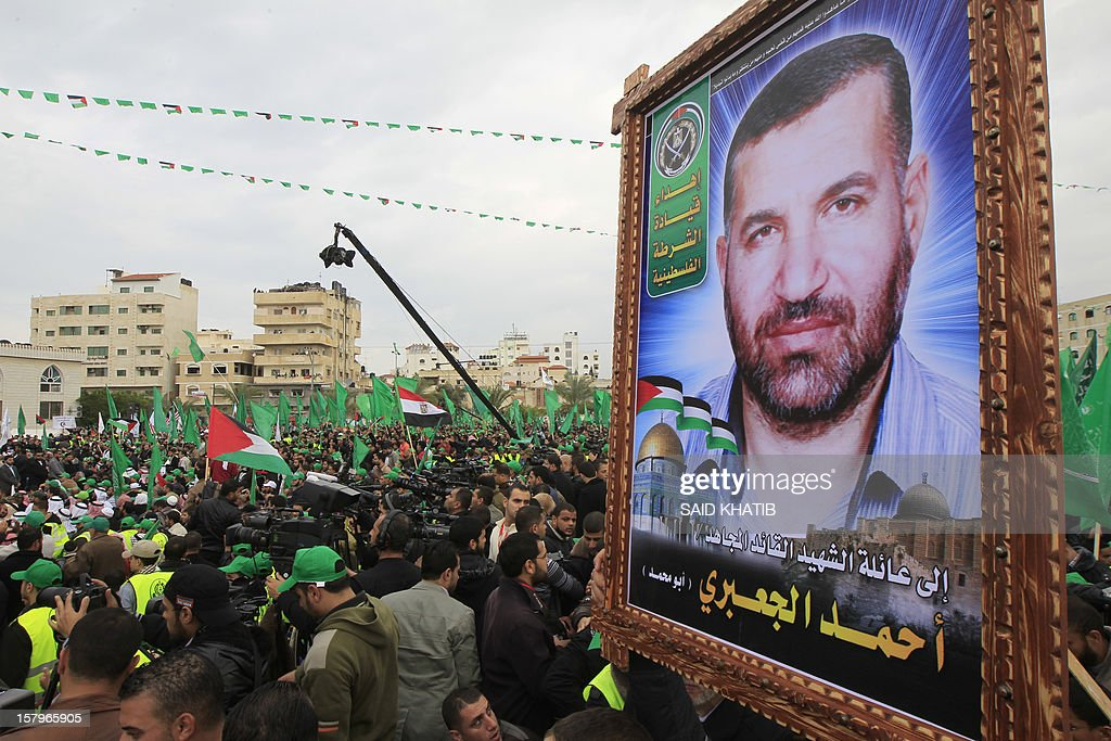 Supporters of Hamas holds of a picture of late Hamas military commander Ahmed Al-Jaabari during a rally to mark the 25th anniversary of the founding of the Islamist movement, in Gaza City on December 8, 2012. Hamas leader in exile Khaled Meshaal made his first visit to Gaza, timed to coincide with the 25th anniversary of the Islamist movement's founding.