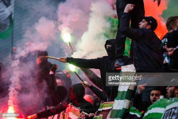 Supporters of Hammarby IF light flares after the 11 equalizing goal during an Allsvenskan match between AIK and Hammarby IF at Friends arena on April...