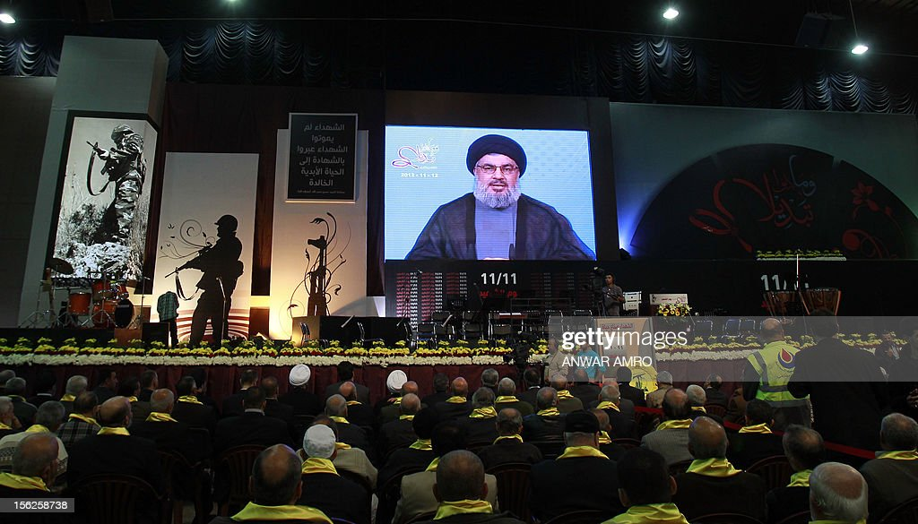 Supporters of Hassan Nasrallah, the head of Lebanon's militant Shiite Muslim movement, watch him speak during a televised address at a rally marking the party's Martyrs' Day in southern Beirut, on November 12, 2012. AFP PHOTO/ANWAR AMRO