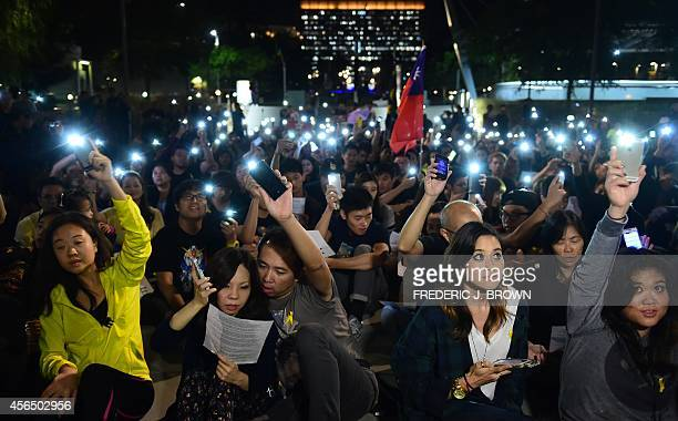 Supporters of Hong Kong's democracy protesters light their cellphones at a downtown park in Los Angeles on October 1 in a show of support for the...
