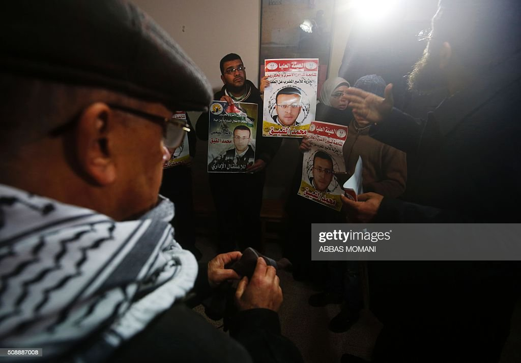 Supporters of hunger striking Palestinian prisoner Mohammed al-Qiq hold portraits as they demonstrates in solidarity with him on February 7, 2016, outside the International Committee of the Red Cross (ICRC) offices in the West Bank city of Ramallah. Qiq will keep up his 10-week hunger strike despite Israel suspending a detention without trial order against him, his lawyer said on February 5. / AFP / ABBAS MOMANI