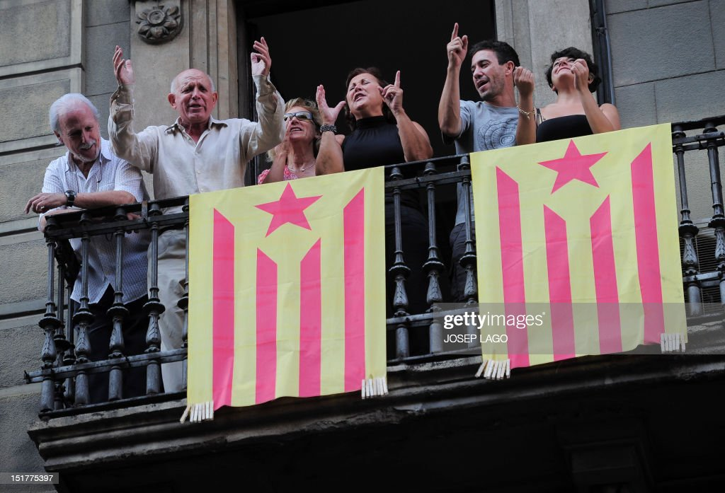 Supporters of independence for Catalonia shout rom a balcony during a demonstration on September 11, 2012 in Barcelona to mark the Spanish region's official day, amid growing protests over Spain's financial crisis which has driven it to seek aid from the central government. Catalonia's leader warned of a 'freedom' bid for the region as tens of thousands of people poured into Barcelona demanding a split from Spain and control of their own economy.