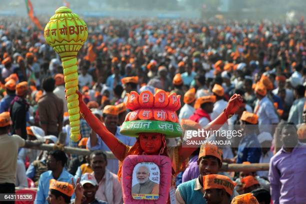 TOPSHOT Supporters of India's Bharatiya Janata Party listen to BJP Leader and Indian Prime Minister Narendra Modi as he speaks during a state...