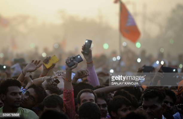 TOPSHOT Supporters of India's Bharatiya Janta Party wave their cellular telephones in the air as they listen to Indian Prime Minister Narendra Modi...