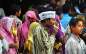 Supporters of India's Congress Party drink from packets of soft drinks which were distributed by party workers during an election campaign rally by...