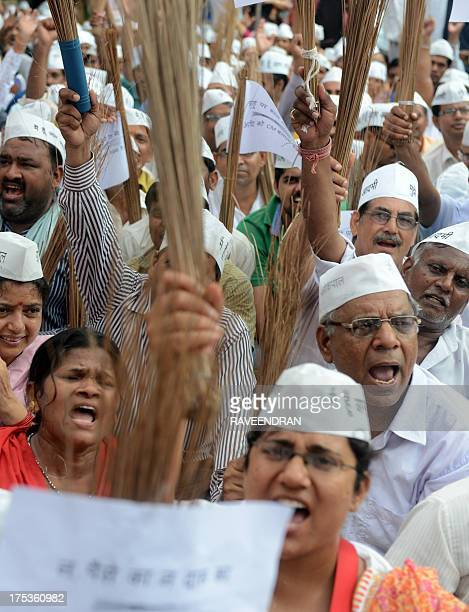 Supporters of India's new party Stand against Corruption 'Aam Aadmi Party' shout slogans as they wave brooms the party symbol during the party symbol...