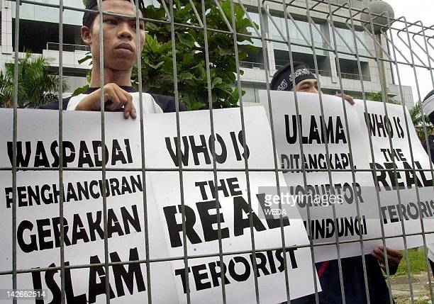 Supporters of Indonesian Muslim cleric Abu Bakar Bashir hold placards during Bashir's trial for treason in Jakarta 23 April 2003 Bashir is charged...