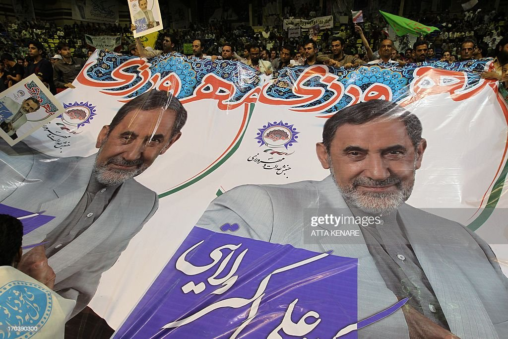 Supporters of Iranian advisor to the supreme leader Ayatollah Ali Khamenei and hopeful conservative presidential candidate, Ali Akbar Velayati hold a giant poster during his campaign rally in Tehran, on June 12, 2013.
