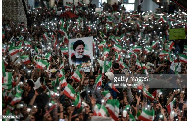 Supporters of Iranian cleric and presidential candidate Ebrahim Raisi wave flags and posters of Raisi during a rally prior to presidential elections...