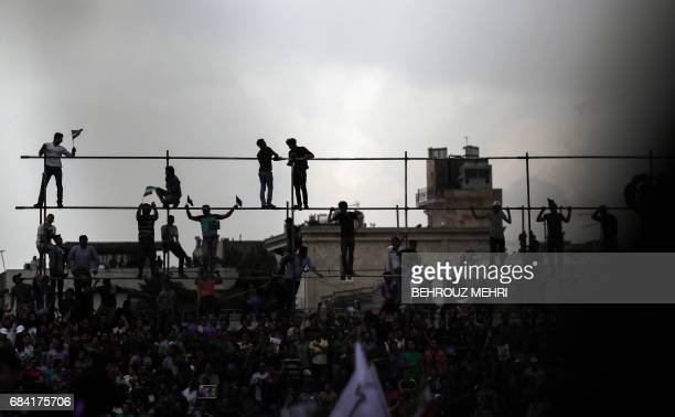 Supporters of Iranian President and candidate in the upcoming presidential elections Hassan Rouhani stand on scaffoldings as they attend a campaign...