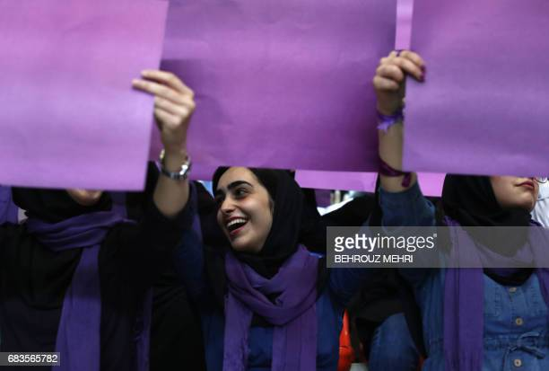 Supporters of Iranian President and presidential candidate Hassan Rouhani hold purple placards the symbol of his movement during an electoral...