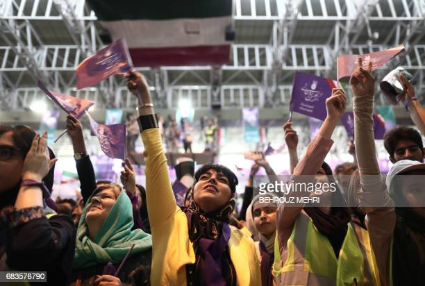 Supporters of Iranian President and presidential candidate Hassan Rouhani chant slogans during an electoral campaign gathering in the northwestern...