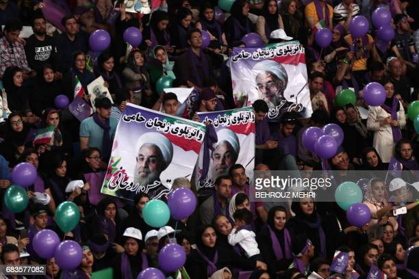 Supporters of Iranian President and presidential candidate Hassan Rouhani hold purple and green balloons purple the symbol of his movement and green...