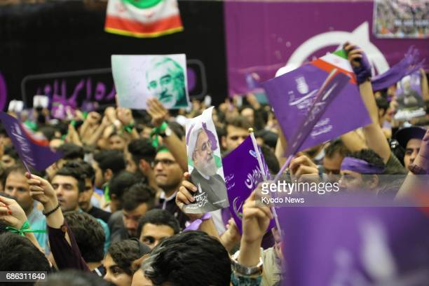 Supporters of Iranian President Hassan Rouhani hold photographs and messages of support in Tehran on May 13 ahead of the May 19 presidential election...