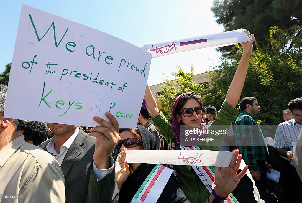 Supporters of Iranian president Hassan Rouhani hold placards and banners as his motorcade leaves Tehran's Mehrabad Airport upon his arrival from New York, on September 28, 2013. Some 60 hardline Islamists chanted 'Death to America' and 'Death to Israel' but they were outnumbered by 200 to 300 supporters of the president who shouted: 'Thank you Rouhani.'