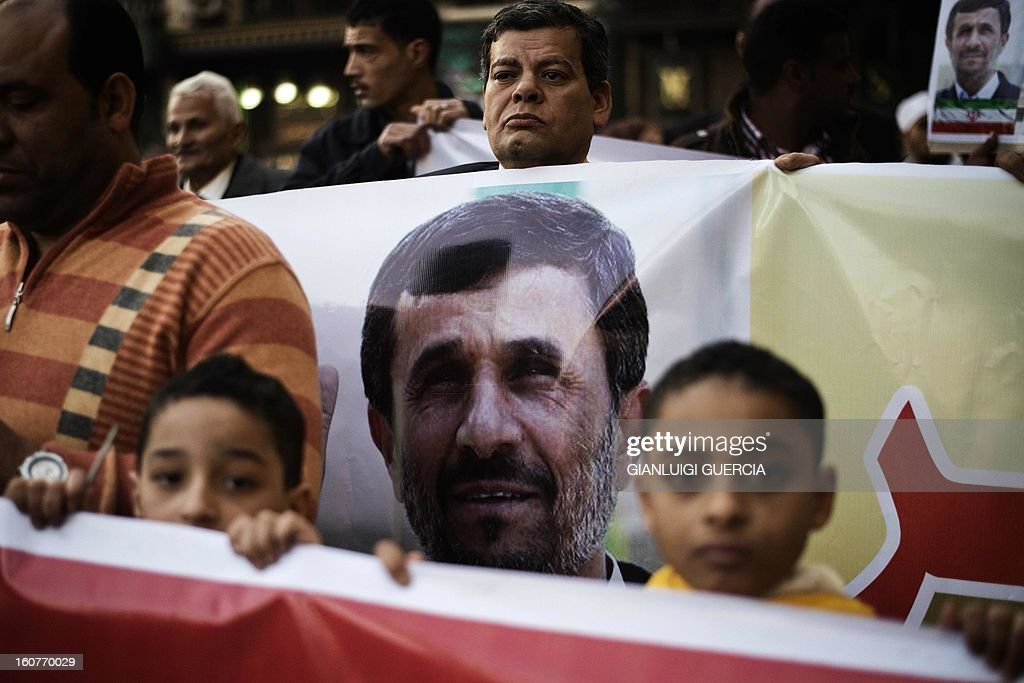 Supporters of Iranian President Mahmoud Ahmadinejad hold his portrait and supporting banners ahead of his official visit to Al-Hussein mosque in Cairo on February 5, 2013. Ahmadinejad held talks in Cairo on the divisive issue of Syria's war, as he kicked off the first visit to Egypt by an Iranian president since 1979. AFP PHOTO/GIANLUIGI GUERCIA
