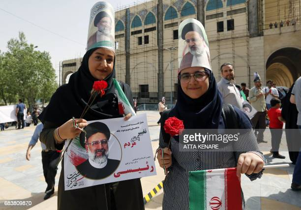 Supporters of Iranian presidential candidate Ebrahim Raisi hold his portrait and wear it on their heads outside a campaign rally at Imam Khomeini...