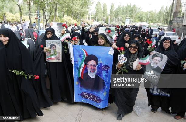 Supporters of Iranian presidential candidate Ebrahim Raisi hold his portrait outside a campaign rally at Imam Khomeini Mosque in the capital Tehran...