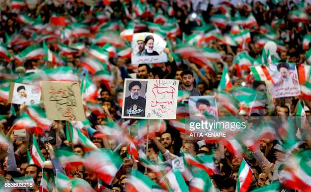 TOPSHOT Supporters of Iranian presidential candidate Ebrahim Raisi wave national flags and raise his portrait as they attend a campaign rally at Imam...