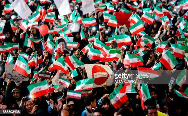 Supporters of Iranian presidential candidate Ebrahim Raisi wave national flags and raise his portrait as they attend a campaign rally at Imam...