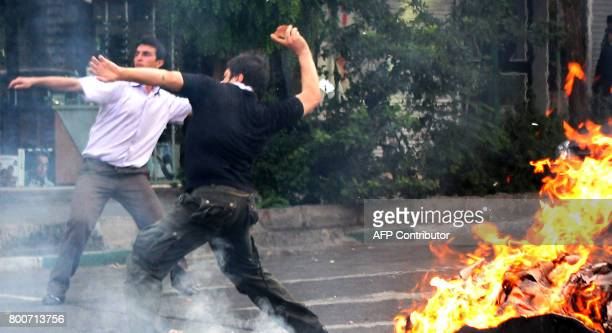 Supporters of Iran's defeated presidential candidate Mir Hossein Mousavi throw stones at riot police during a demonstration in Tehran on June 20 2009...