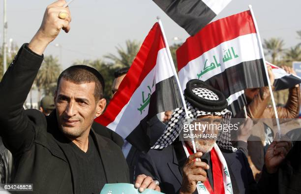 Supporters of Iraqi cleric Moqtada alSadr wave their national flag as they demonstrate in Baghdad on February 8 2017 to demand electoral reform ahead...