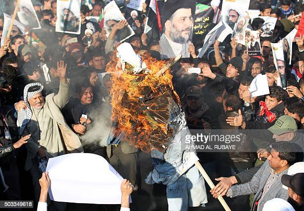 Supporters of Iraqi Shiite cleric Moqtada alSadr burn a effigy of a member of the Saudi ruling family as others hold posters of prominent Shiite...