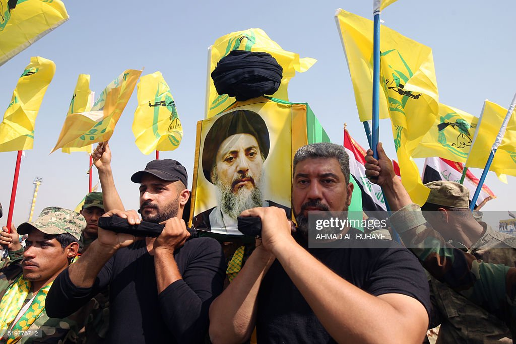 Supporters of Iraqi Shiite Muslim leader Ammar alHakim head of the Islamic Supreme Council of Iraq carry a mock coffin during a rallye commemorating...