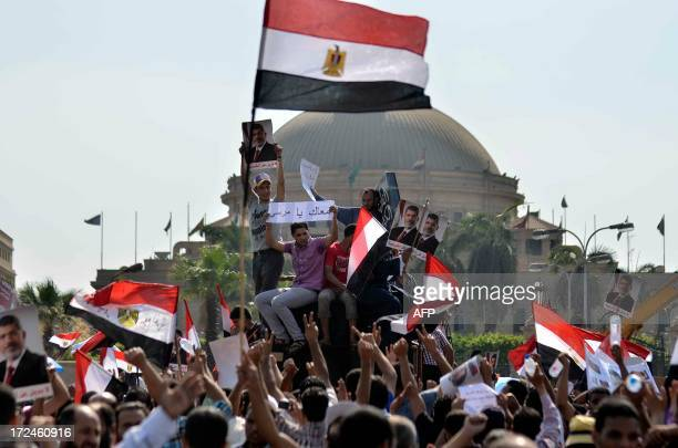Supporters of Islamist Egyptian President Mohamed Morsi hold pictures of him during a rally by mainly Muslim Brotherhood partisans outside Cairo...