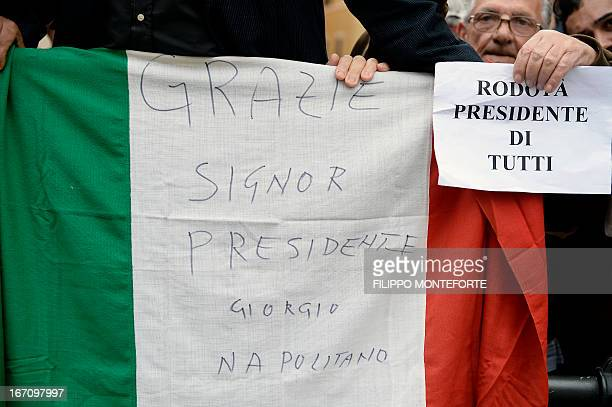 Supporters of Italy's President Giorgio Napolitano hold an Italian flag reading 'Thanks mister President Giorgio Napolitano' and a Five Stars...