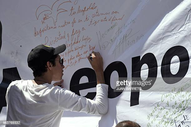 Supporters of jailed opposition leader Leopoldo Lopez leaves a message on a banner during a demonstration in Caracas on February 18 2015 Venezuelan...