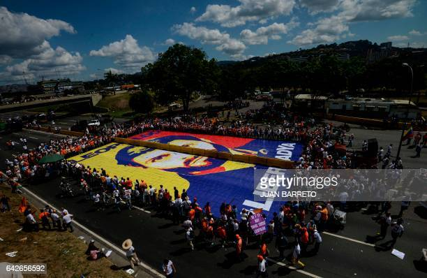 Supporters of jailed Venezuelan opposition leader Leopoldo Lopez surround a giant image of him during a demonstration held on the third anniversary...