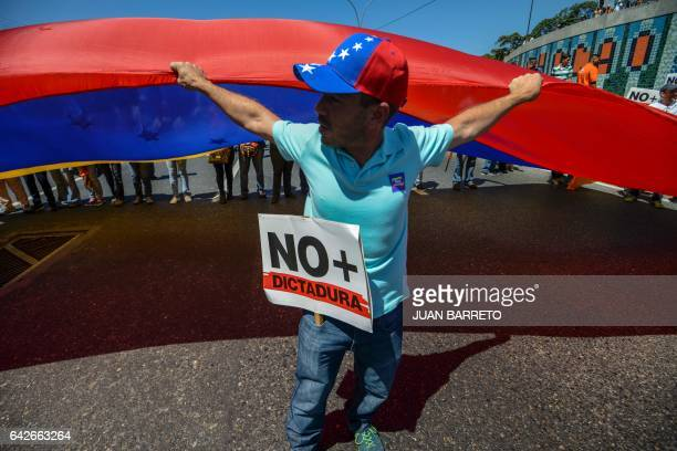 Supporters of jailed Venezuelan opposition leader Leopoldo Lopez carry a huge Venezuelan flag during a demonstration held on the third anniversary of...