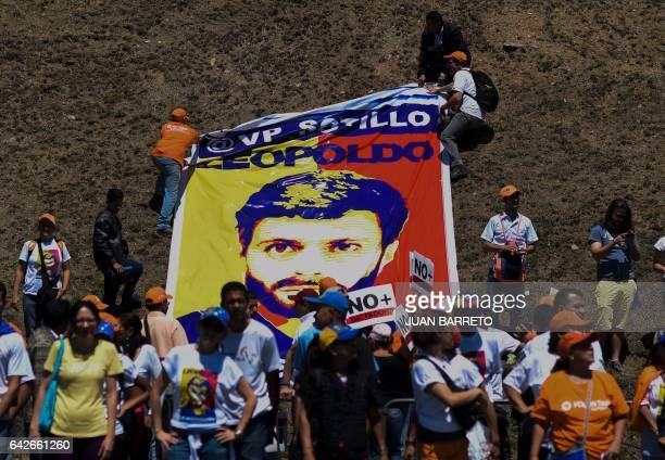 Supporters of jailed Venezuelan opposition leader Leopoldo Lopez lay down a poster of him during a demonstration held on the third anniversary of his...