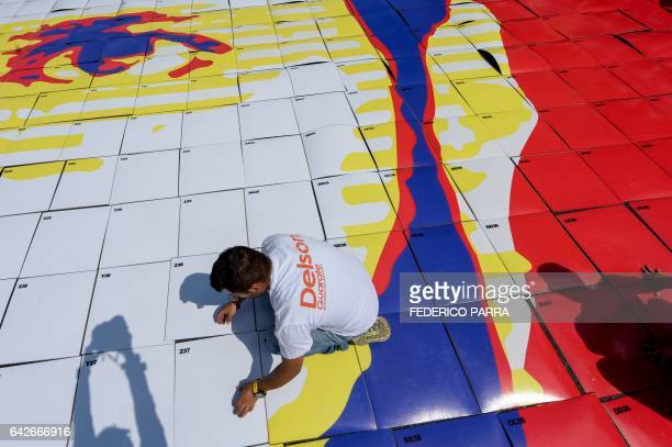 Supporters of jailed Venezuelan opposition leader Leopoldo Lopez lay down the pieces of a giant image of him during a demonstration held on the third...