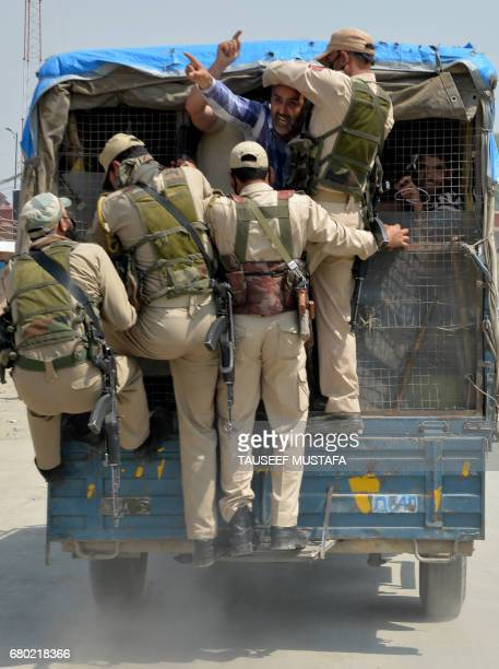 Supporters of Jammu and Kashmir lawmaker Sheikh Engineer shout slogans from a police vehicle after being detained by Indian police during a march...
